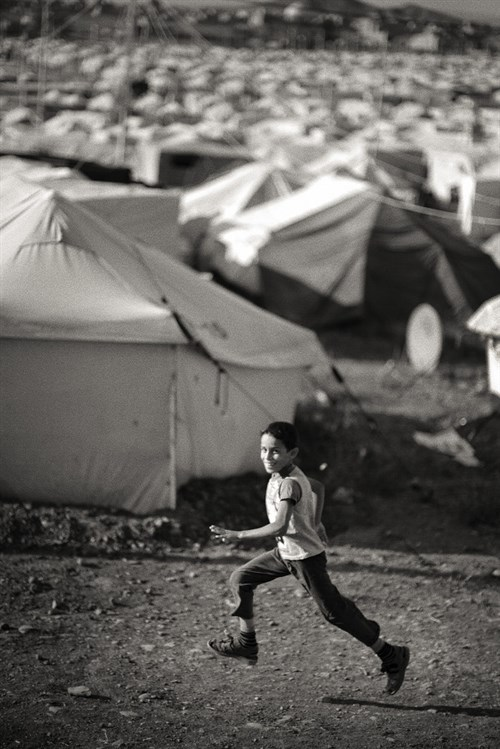 A Boy Runs Past Tents 599X897